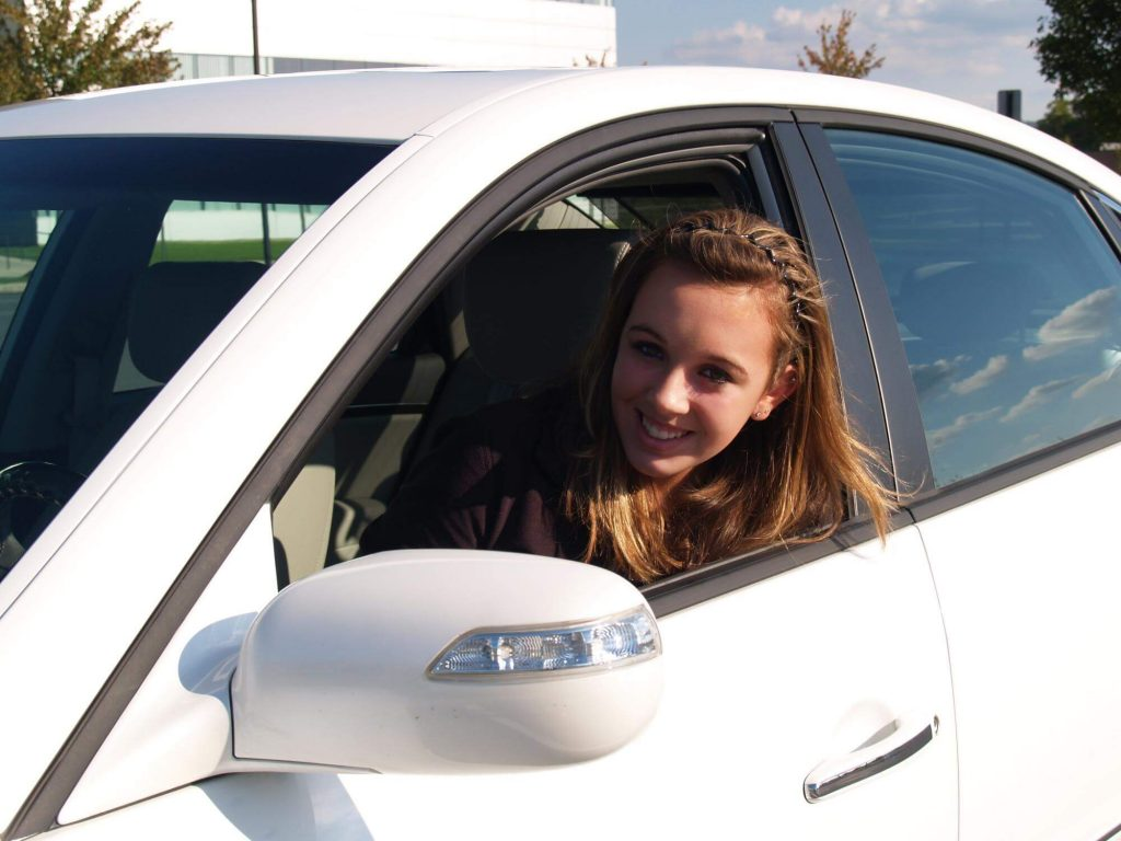 A happy driving school student looking through the side window of one of our cars